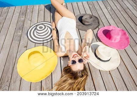 Beautiful smiling woman in swimsuit lying with colorful sunhats on the wooden poolside. Top view. Summer vacation concept