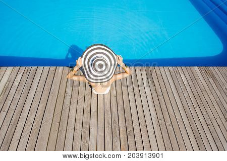 Woman in big sunhat sitting back on the poolside with blue water background. Top wide angle view