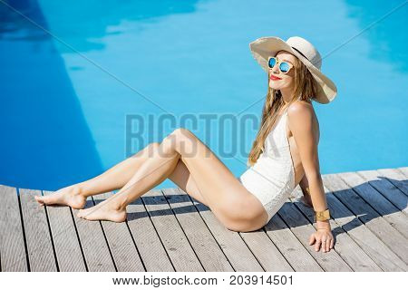 Beautiful young woman in sunhat and swimsuit relaxing near the swimming pool sitting on the wooden poolside