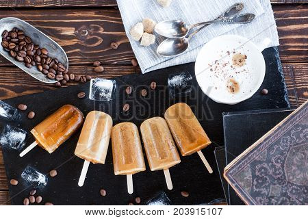 Coffee espresso and milk popsicles with coffee beans on dark stone board over wooden table. Ice pops, Summer dessert. Ice cream, Frozen drink. Decorated with coffee cup and books. Vintage retro style.
