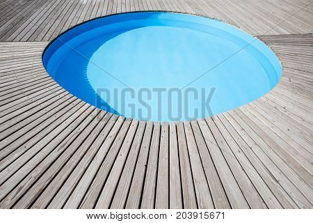Round swimming pool with wooden poolside oudoors