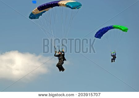 Kharkiv Ukraine - August 26 2017: Skydiver flying on colorful parachute at the airfield Korotych Kharkov region Ukraine on August 26 2017