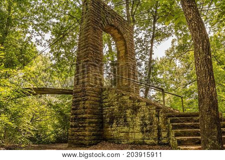 An arched stone entrance to a swinging bridge in the appalachian forest in Tishomingo County Mississippi.