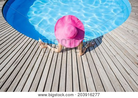 Woman in big pink sunhat with cocktail drink relaxing at the round swimming pool with blue water outdoors. Top view
