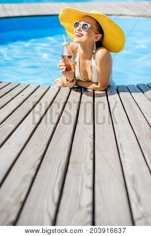 Young woman in swimsuit with big yellow sunhat relaxing with a bottle of fresh drink sitting on the poolside outdoors