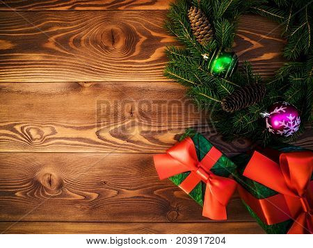 Christmas wreath of fir branches with cones and fir tree balls along with gift boxes on the wooden background. Top view. Holiday concept