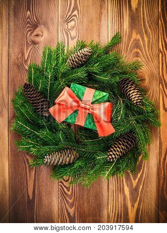 Christmas wreath of fir branches with cones along with gift box on the wooden background. Top view. Holiday concept
