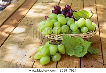 Basket of white grapes on a wooden surface
