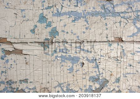 Texture, pattern, background. old paint. the wooden wall cracked with paint. With a white tinge, the paint eventually peels off
