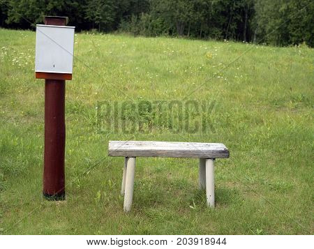 Post box and wooden bench in the open field a forest in the background