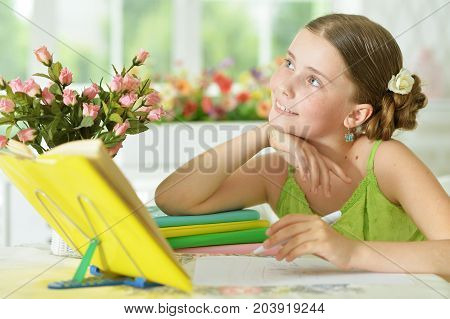 Cute schoolgirl sitting at table and doing homework at home