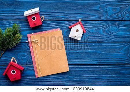 house toys to decorate christmas tree for new year celebration with fur tree branches and notebook on blue wooden table background top veiw mockup