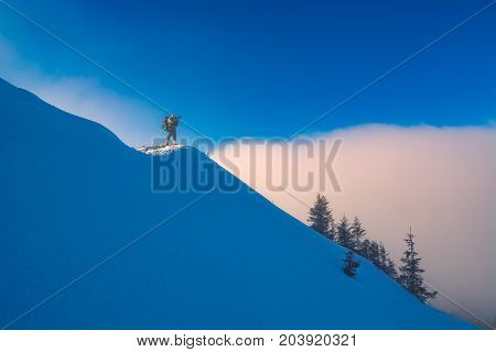 Photographer standing on a snowy hill and taking photos of beautiful winter misty mountain valley. Carpathians Ukraine Europe.