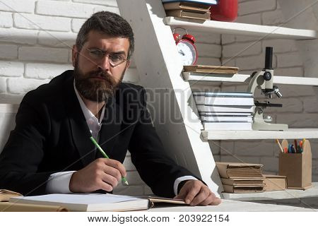 Teacher and school supplies in classroom. Man with beard on white brick wall background. Professor with serious face expression writes in notebook. Education and knowledge concept