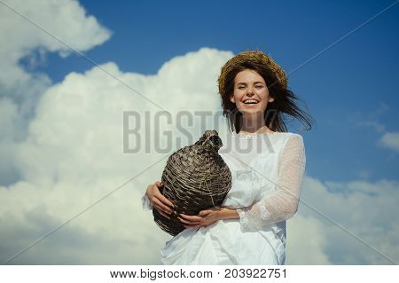 Happy girl smiling with wicker wine bottle on cloudy sky. Harvesting and winemaking. Winery tour concept. Summer vacation holidays and celebration. Woman in white dress and wreath on brunette hair.