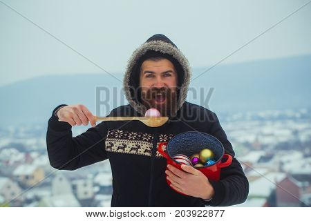 Bearded Man Eating Xmas Balls With Wooden Spoon From Pot
