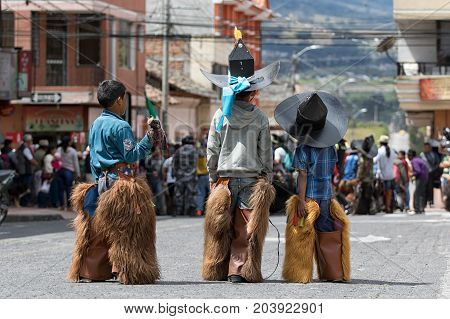 June 24 2017 Cotacachi Ecuador: indigenous quechua children dressed in chaps watching the adults performing the Inti Raymi parade