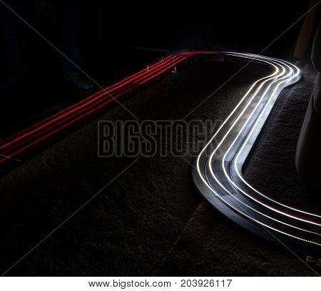 Utilizing two slot cars with headlights and taillights to paint with light.