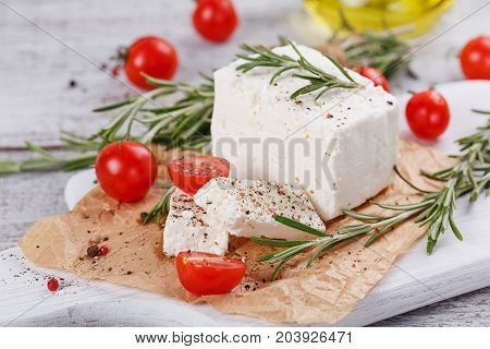 Fresh feta cheese with cherry tomatoes and rosemary on white wooden serving board over light wooden background. Close up.