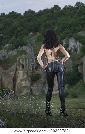 Young girl wearing latex pants posing outdoor