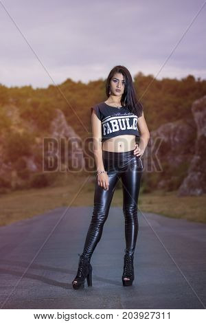 Young girl wearing tshirt and latex pants posing outdoor