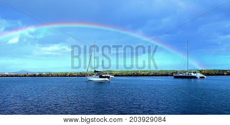 Natures beauty a colourful vibrant Rainbow in a stormy blue sky over water with boats next to a break-wall. Photographed in the safe haven of Iluka harbour on the Clarence river New South Wales Australia.