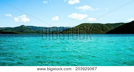 Tropical Paradise - Marinescape. This Island Head anchorage is postcard stuff with crystal clear turquoise water bold heavily timbered hills in the foreground with vivid distant mountains as a backdrop.