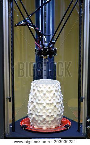 A white vase is standing inside a 3d printer close-up. Progressive modern additive technologies 4.0 industrial revolution