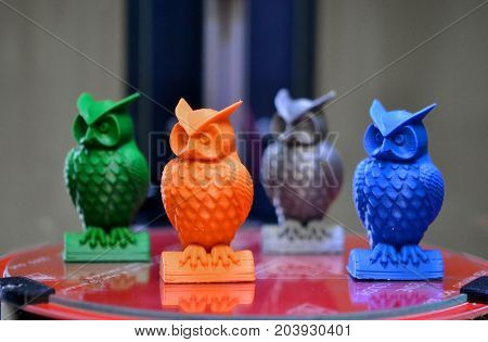 Four multicolored models of owls created on a 3d printer stand on the desktop of 3d printer close-up. Progressive modern additive technologies 4.0 industrial revolution