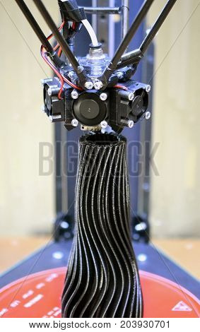 The three-axis 3d printer creates an object in the form of a black vase close-up. Progressive modern additive technologies 4.0 industrial revolution