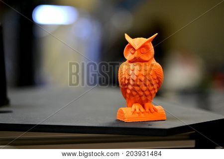 Orange owl object printed by 3d printer stands on blurry dark background close-up. Progressive modern additive technologies 4.0 industrial revolution
