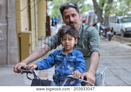 Fars Province Shiraz Iran - 18 april 2017: A family of two people a father and a boy about 5 years old ride a motorbike along a city street.