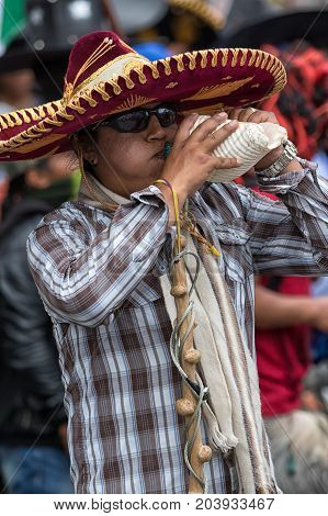 June 24 2017 Cotacachi Ecuador: man using conch shell to make noise at the Inti Raymi parade
