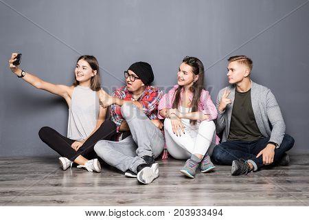 Happy Friends Taking Selfie While Sitting On Floor