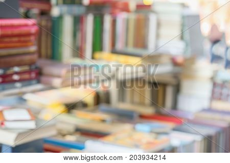 Many books, textbooks or fiction in rows lying on the table, on the shelves in library or in modern urban bookshop. Self-study, educational, manuals, textbooks, school, study concept. Blurred abstract background