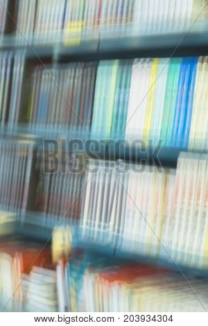 Abstract blurred books, manuals and textbooks on bookshelfs in in library or in book store on vertical background. Concept for education, Reading fiction