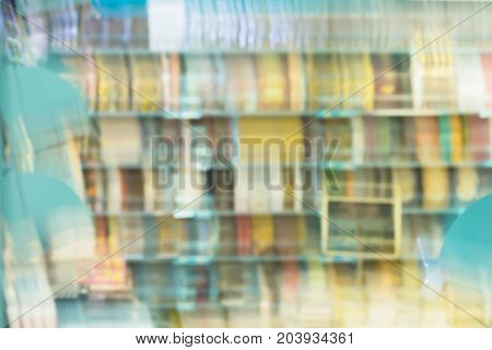 Abstract blurred books, manuals and textbooks on bookshelves in library or in book store, for background. Concept for education