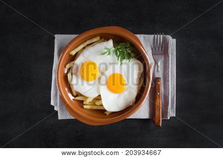 Traditional spanish lunch - fried eggs with french fries, cured pork slices of jamon on the black chalkboard. Top view