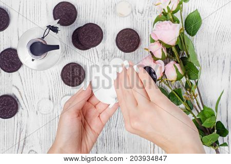 Female hand cream cotton pad cookie flowers on a white wooden background