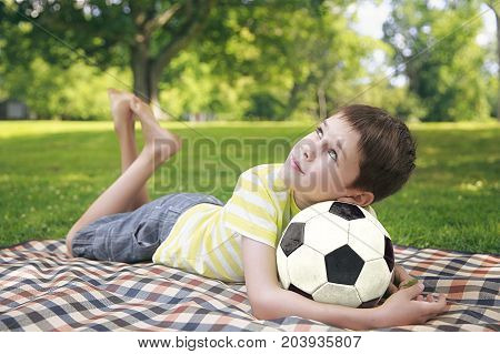 Boy resting with a soccer ball. cute kid lying in the park relaxing after active games at the picnic. looking up. Copy space for your text