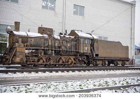 Old rusty abandoned steam engine on railroad in winter