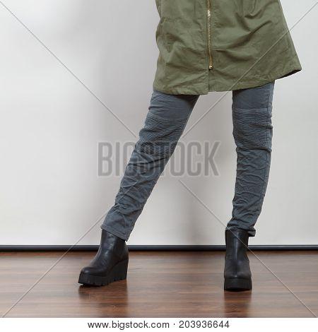 Closeup of woman girl in dark green khaki coat and winter boots posing in studio. Autumn fall fashion.