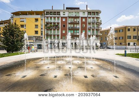 VERONA ITALY - JUNE 25 2016: Picture from Piazza Cittadella with a water fountain and residential buildings in a sunny day with clouds. Verona Italy.