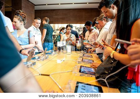 STRASBOURG FRANCE - APR 27 2016: Group of adults kids customers testing playing on the latest iPhone smartphone in Apple Store.