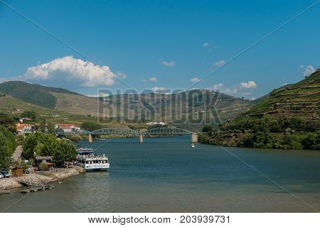 PESO DA REGUA PORTUGAL - JULY 8 2017: Bridge and quay over the river Douro valley Peso da Regua Portugal