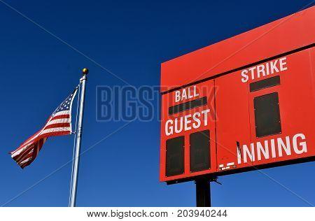 The American flag is adjacent to a baseball scoreboard