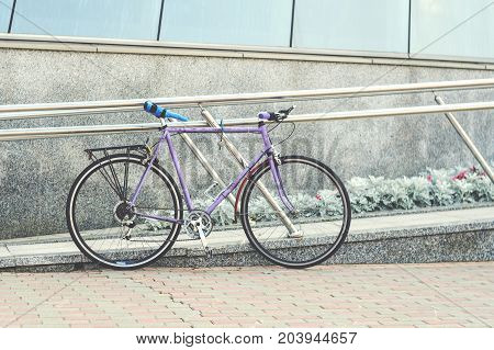Old road bike of pink color with a ridiculous seat rewound blue electrical tape. Cycling or commuting in city urban environment ecological transportation concept