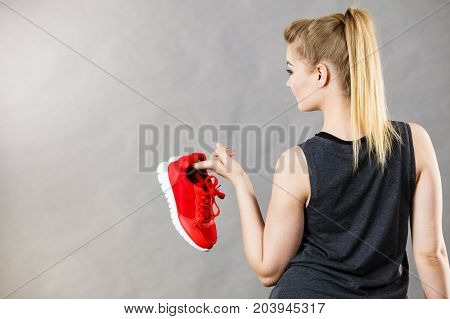 Sporty woman presenting sportswear trainers red shoes comfortable footwear perfect for workout and training.
