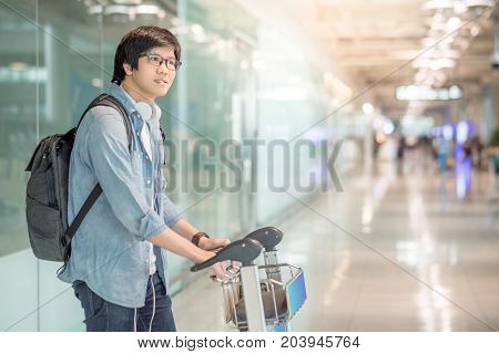 Young Asian man walking with airport trolley and his suitcase luggage in the international airport terminal arrival from travel abroad