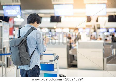 young asian check in online by using smartphone and waiting for drop his luggage at airline check-in counter inside the international airport terminal travel lifestyle concept